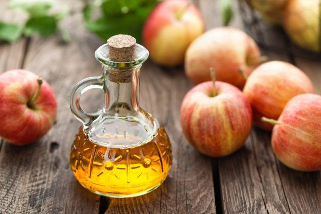 Apple cider vinegar in a bottle and apples on a wooden table.