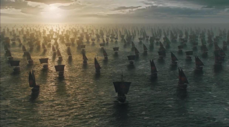 A fleet of ships sailing toward the camera at sunset
