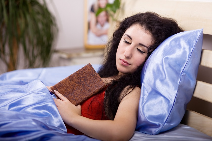 Woman falling asleep while reading a book in bed.
