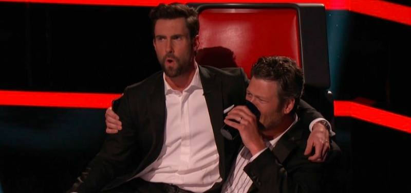 Blake Shelton is drinking from a mug while Adam Levine sits in his lap on the set of The Voice