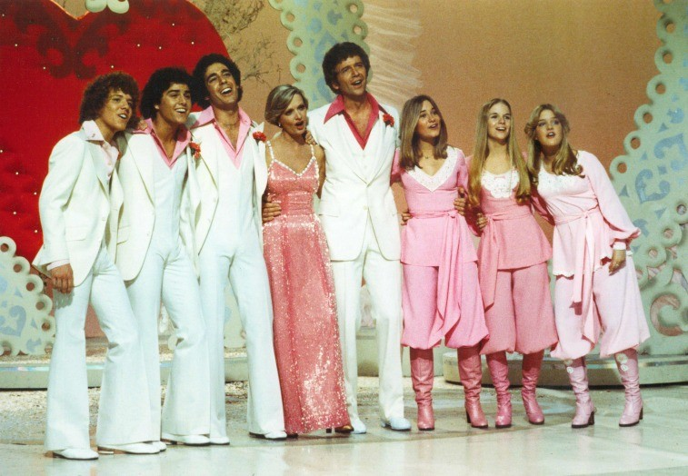 Eight-person family on stage in white and pink attire with Valentine's decorations behind them