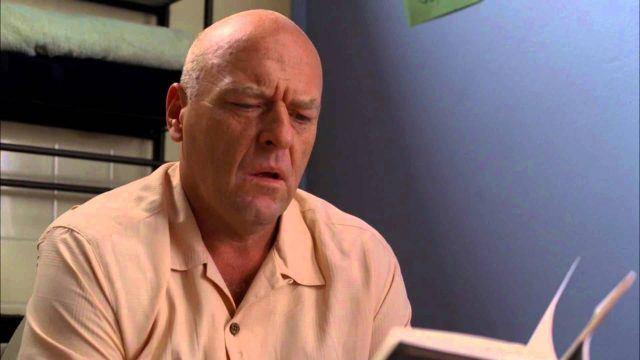 Hank sitting on the toilet and reading a book of Walt Whitman poetry in a scene from the AMC series 'Breaking Bad'