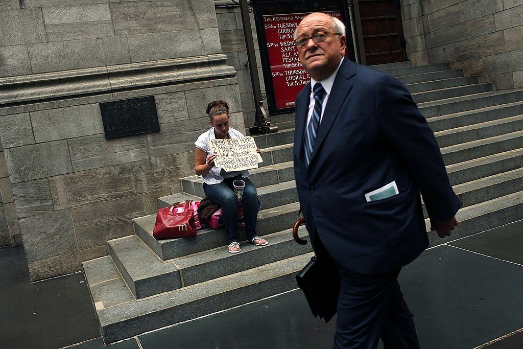 A businessman walks by a homeless woman in New York City.