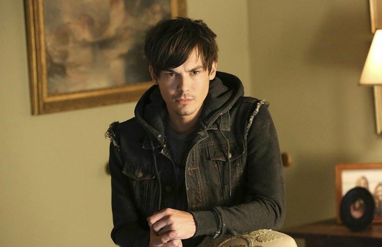 Caleb Rivers young man in a black hoodie and black denim vest in a tan room with a framed painting