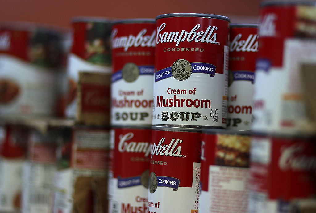 Cans of Campbell's soup are displayed on a supermarket shelf