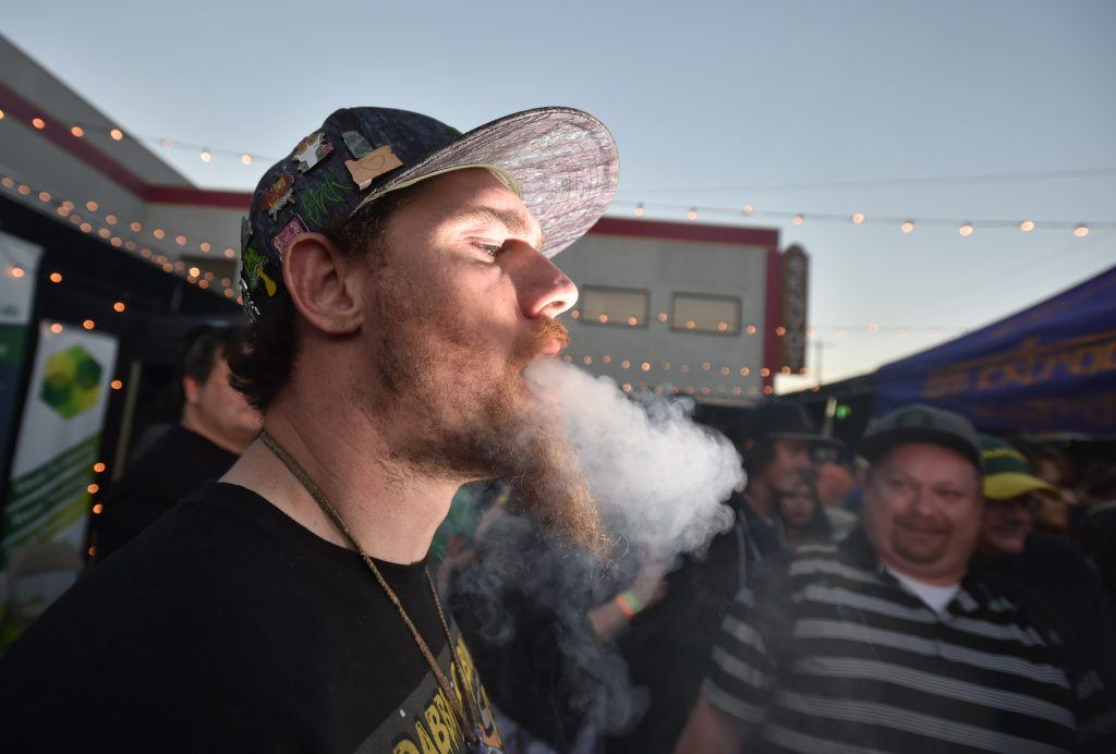 A man smokes a joint at the first annual DOPE Cup, a cannabis competition in Portland, Oregon