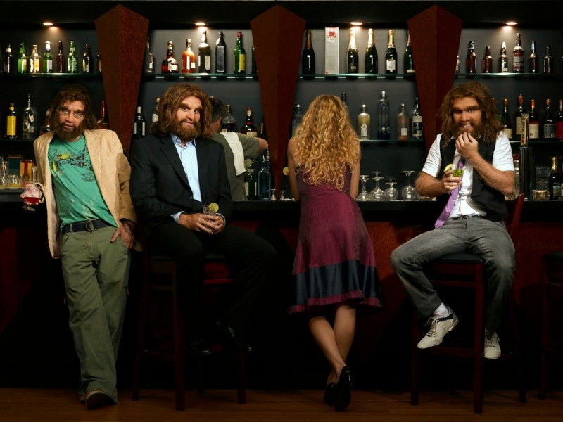 Three well-dressed cavemen in a bar with a woman facing away