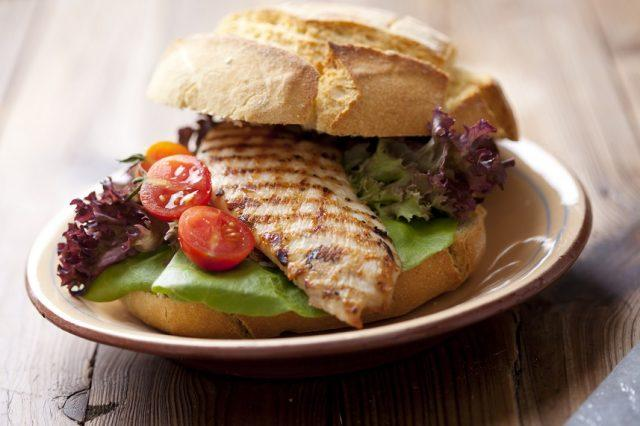 Grilled chicken sandwich on a place with lettuce and tomato.