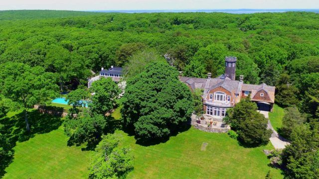 An aerial view of Tower Hill shows the home surrounded by forest and a large yard.