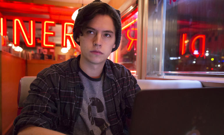 Cole Sprouse's Jughead sits at a booth in a diner in the CW's Riverdale