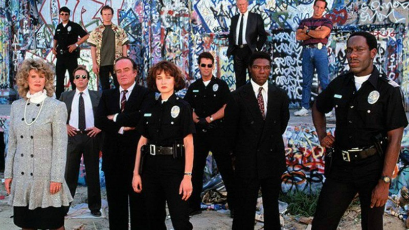 Group of 11 people some police officers standing in front of graffiti