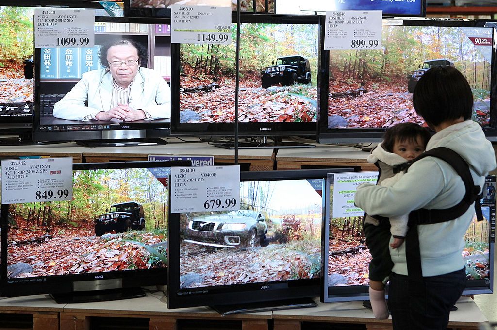 A Costco customer looks at a display of flat screen TVs