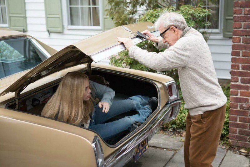 A man standing over a car looking in the trunk at a girl