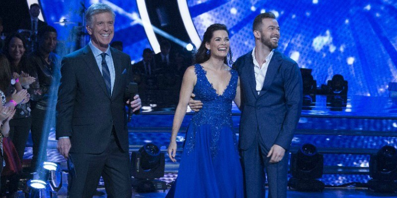 Nancy Kerrigan and Artem Chigvintsex have their arms around each other smiling. Tom Bergeron is standing next to them on stage.