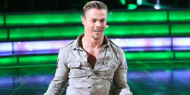 Derek Hough in a khaki shirt dancing and performing.