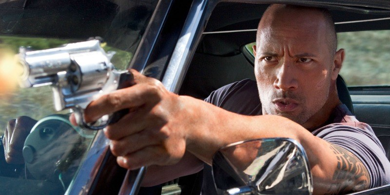 Dwayne Johnson has his arm out of a car pointing a gun.