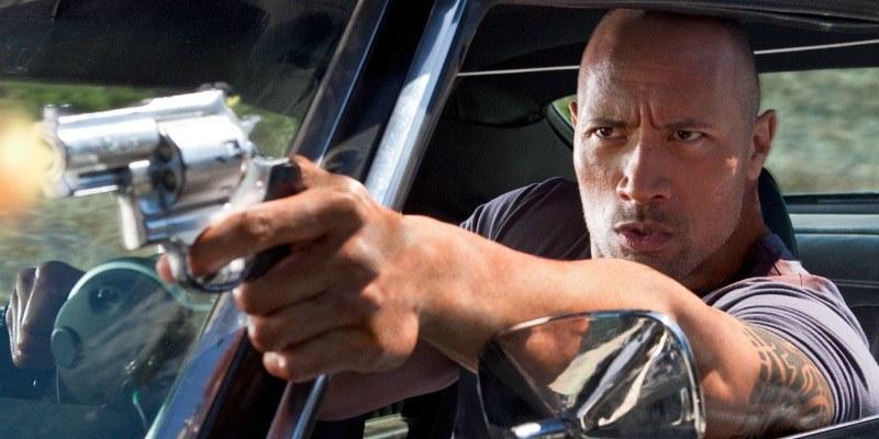 Dwayne Johnson has his arm out of a car pointing a gun.