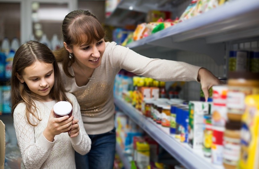 Female with daughter choosing canned goods