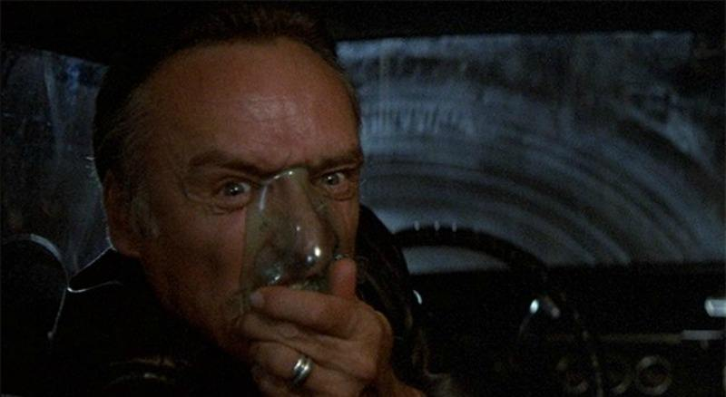 Frank Booth is in a car and turns around to the backseat and puts an oxygen mask on his face.