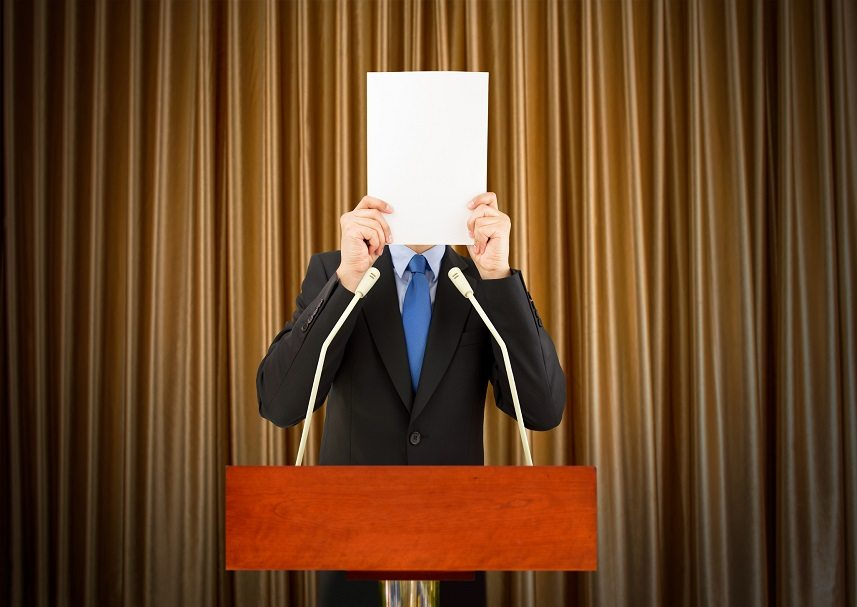 businessman with stage fright covering his face