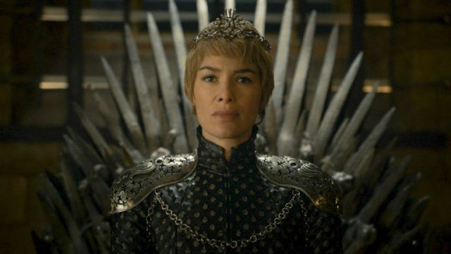 Cersei in all black, wearing a crown, and sitting atop the Iron Throne.
