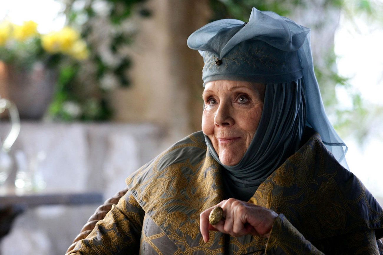 Lady Olenna, wearing a blue headdress, and smiling while sitting down.