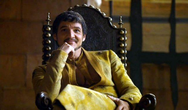 Oberyn Martell sits with his chin on his hand and smiles in a scene from 'Game of Thrones.'