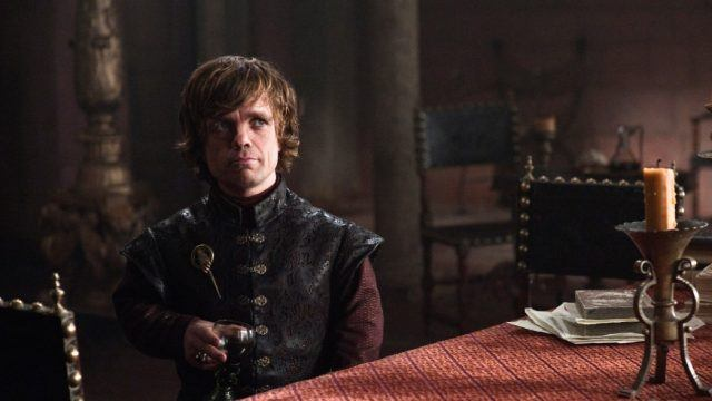 Tyrion Lannister holds a glass of wine and looks amused in a scene from 'Game of Thrones.'