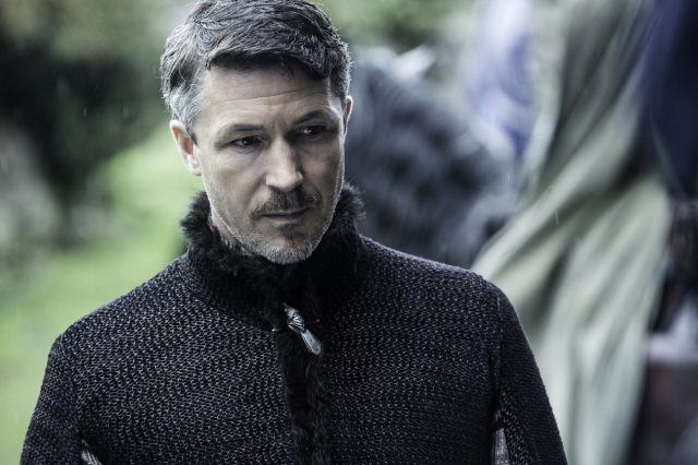 Petyr Baelish looks forward while wearing a black suit.