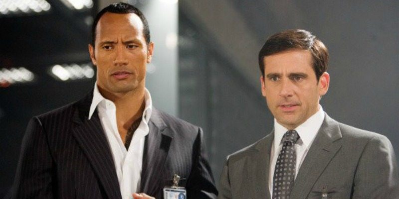 Dwayne Johnson and Steve Carrell stand next to each other in suits for Get Smart.