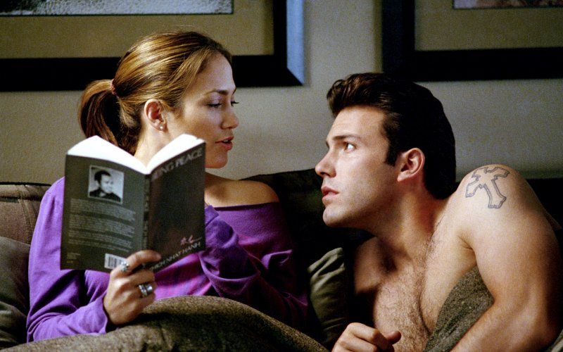 Jennifer Lopez reads a book in bed, while a shirtless Ben Affleck looks up at her from a prone position