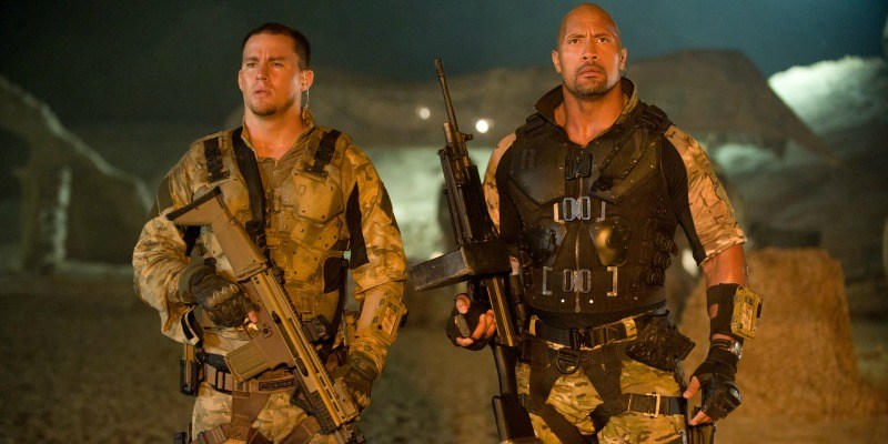 Channing Tatum and Dwayne Johnson are dressed as military men and holding guns.