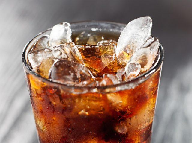 Glass of cola drink with ice, shot close up with selective focus.