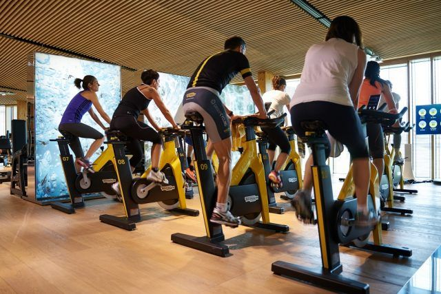 A group of people take a spin class at a studio.