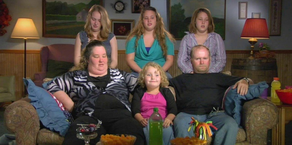 Six family members pose sitting on and standing behind a couch