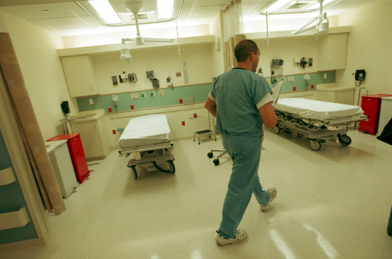 An emergency room nurse walks through a hospital unit