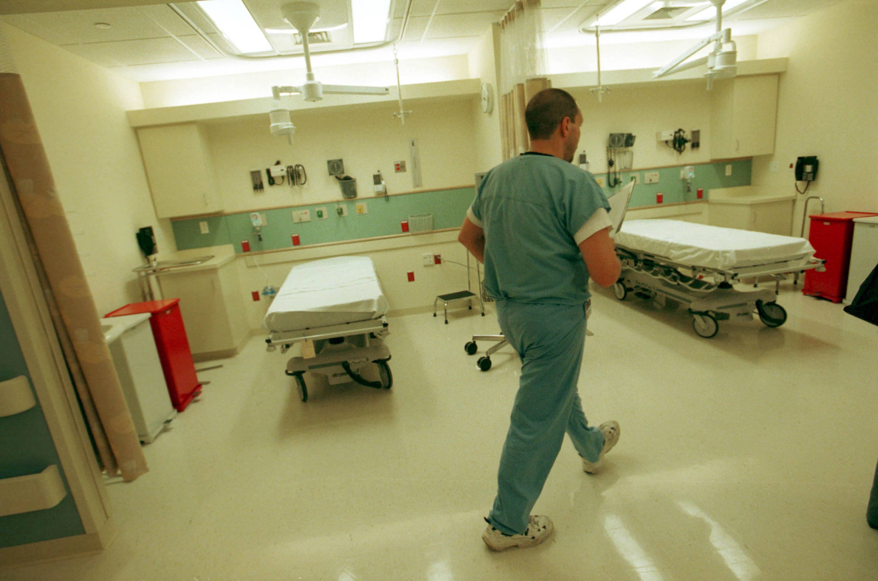 An emergency room nurse walks through a hospital unit