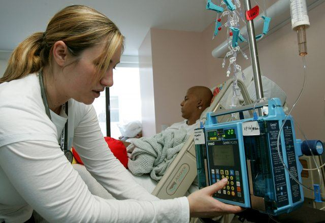 Registered nurse Autumn Small adjusts an IV drip machine for eighteen-year-old cancer patient Patrick McGill
