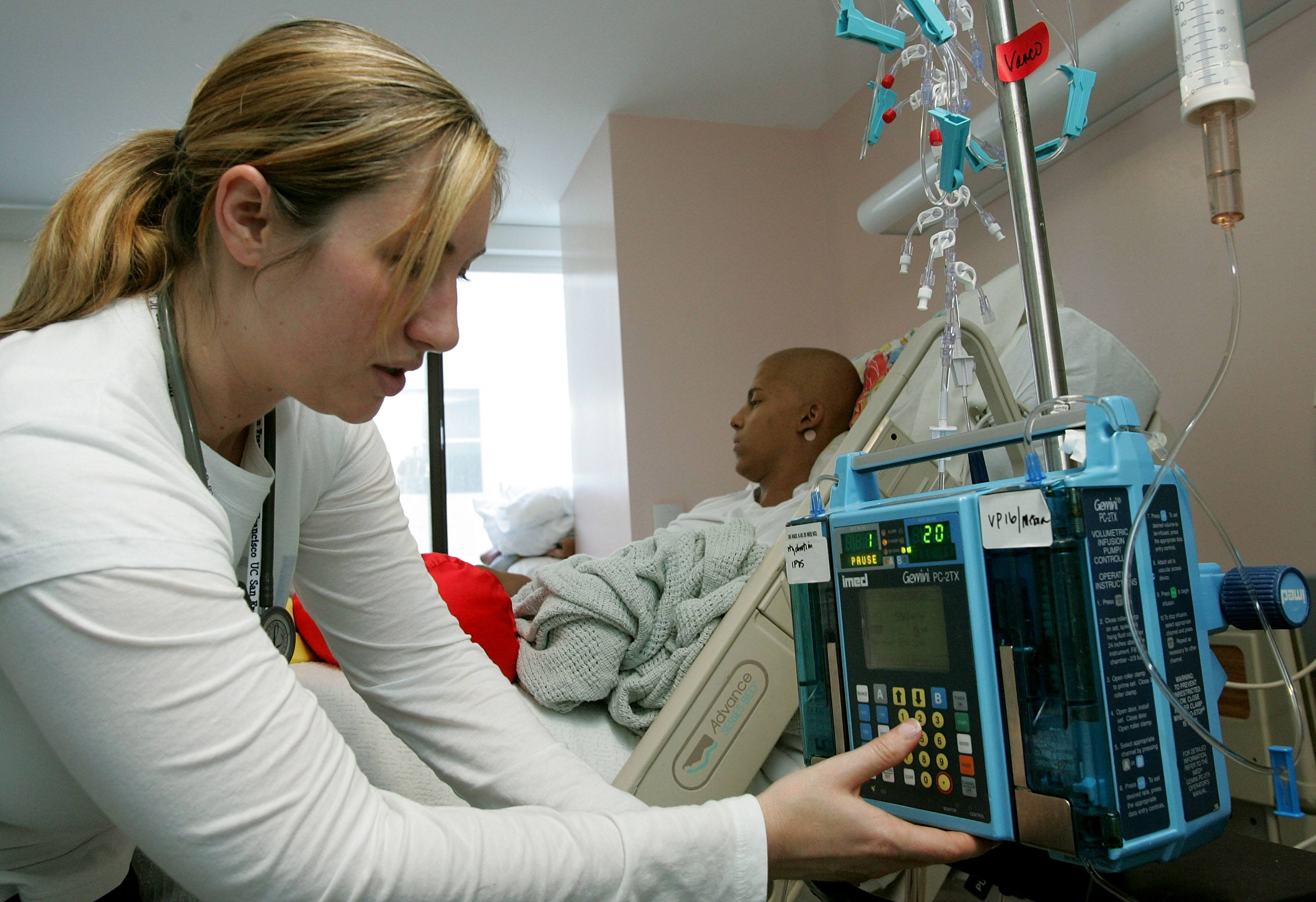 Registered nurse Autumn Small adjusts an IV drip machine for an eighteen-year-old cancer patient