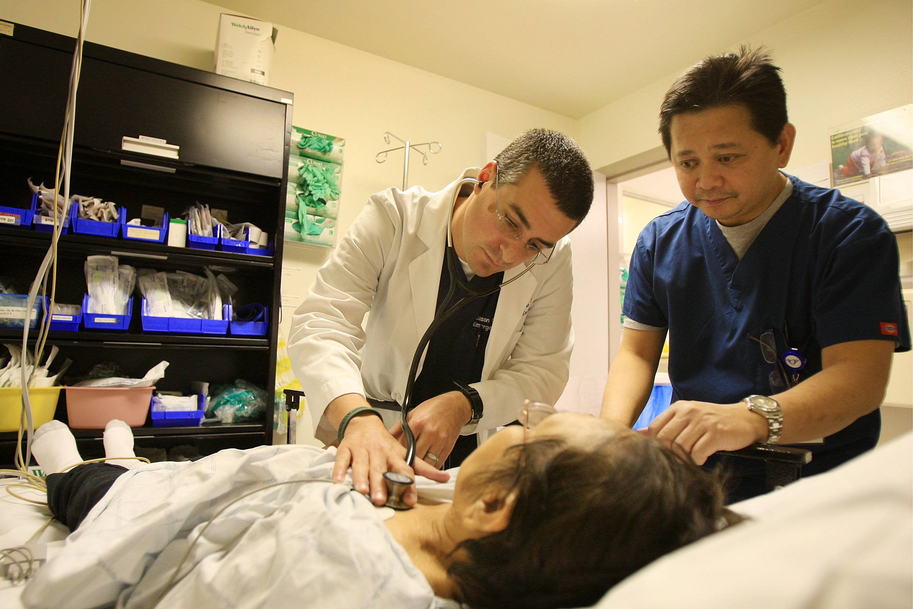 Health care workers care for a patient in the ER