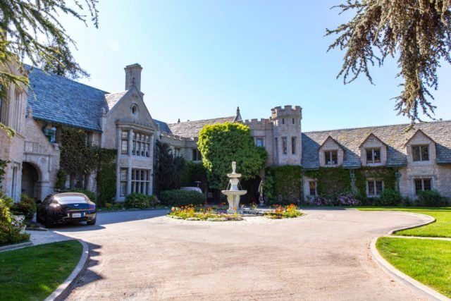 Hugh Hefner's Playboy Mansion has a circular driveway and a fountain in the entrance.