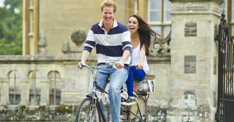 A man and a woman on a tandem bicycle riding outside a castle