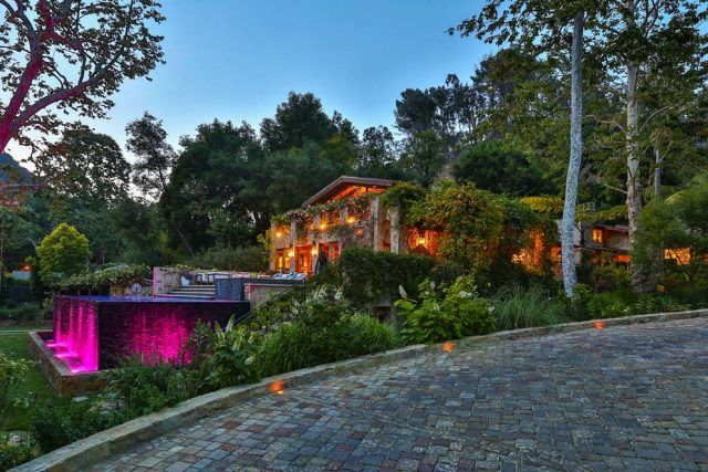 The exterior of Jennifer Lopez's new home features ambient lighting, a large patio and several tall, lush trees.