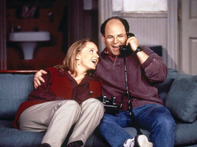 Susan (Heidi Swedberg) leans on George's (Jason Alexander) shoulder as he talks on the phone in a scene from 'Seinfeld'