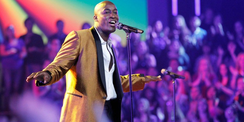 Jermain Paul is singing in a suit on stage of the show.