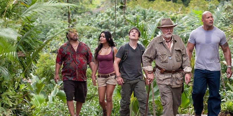 The cast of Journey 2: The Mysterious Island is walking together in a jungle.