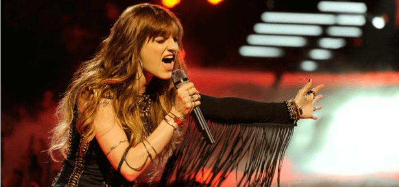 Juliet Simms is singing on stage and has her arm stretched out before her.