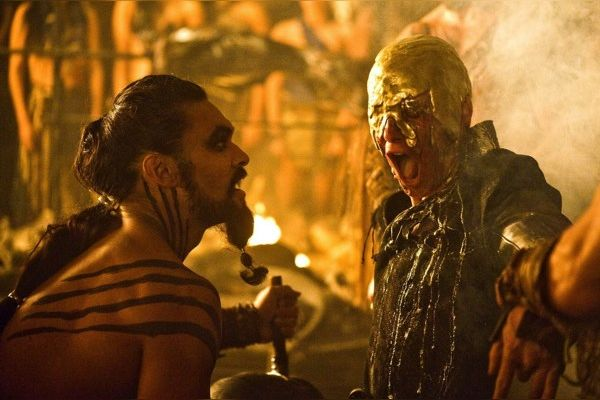 Khal Drogo looks closely at Daenerys' brother who has melted gold on his head.
