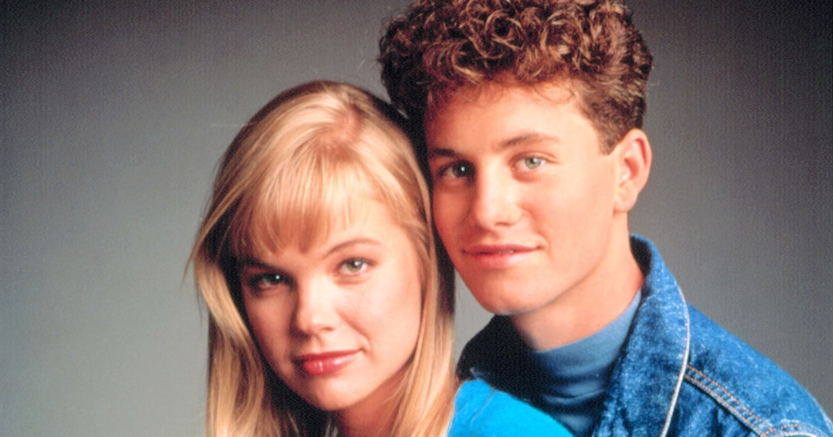 A young Kirk Cameron and Julie McCullough pose for a photo in blue shirts