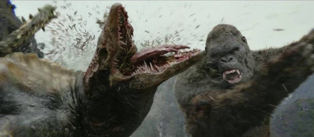 Kong hits a monster in the head with a tree trunk